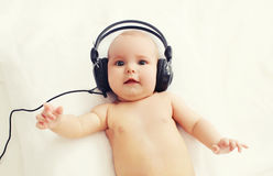 Beautiful baby listens to music in headphones lying on bed