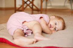 Beautiful baby lying on a blanket. Baby girl of seven months old on floor Stock Photography