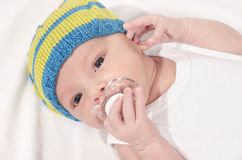 Beautiful baby lying down on white sheets with a pacifier in his mouth. Cute new born baby boy wearing a hat holding a binky Royalty Free Stock Photography