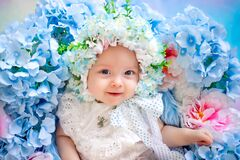 Beautiful baby 6 months in a hat made of flowers, lying in a basket with hydrangeas, a small child among flowers