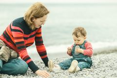 Beautiful baby with mother play on the beach. One-year-old child holds stones in his hands. Baby in denim overall sits near water edge in spring. Happy family royalty free stock photo