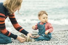 Beautiful baby with mother play on the beach. One-year-old child puts a small stone in mom hand. Baby girl in denim overall sits near water edge. Happy family stock photography