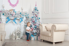 Beautiful baby near a Christmas tree. Beautiful baby girl near a Christmas tree with presents and holding a toy Royalty Free Stock Photos