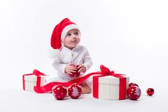 Beautiful baby in the New Year`s cap and white body sits among b. Oxes of holiday gifts and Christmas balls, picture with depth of field royalty free stock photography
