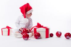 Beautiful baby in the New Year`s cap and white body sits among b. Oxes of holiday gifts and Christmas balls, picture with depth of field stock photo