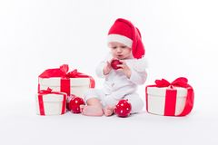 Beautiful baby in the New Year`s cap and white body sits among b. Oxes of holiday gifts and Christmas balls, picture with depth of field stock photography