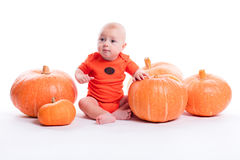 Beautiful baby in orange t-shirt on a white background sits next stock photos