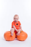 Beautiful baby in orange t-shirt on a white background sitting o stock photos