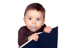 Beautiful baby with a pacifier reading Royalty Free Stock Photos