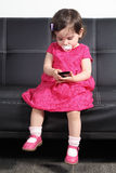 Beautiful baby playing with a smart phone at home Royalty Free Stock Images