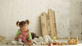 A beautiful baby plays on the floor with wooden cubes. Educational toys. Preschool education. Kindergarten.  stock video
