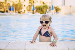 Beautiful baby in the pool happily smiling in sunglasses Stock Image