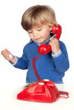Beautiful baby with a red phone Stock Images