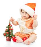 Beautiful baby in santa hat near christmas tree Stock Images