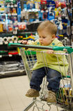 Beautiful baby in shopping cart - trolley. In a mall Royalty Free Stock Image