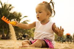Beautiful baby sits facing the camera and playing with toy rake in the sand on the beach. Royalty Free Stock Photography
