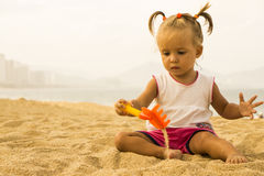 Beautiful baby sits facing the camera and playing  with toy rake in the sand on the beach. Royalty Free Stock Photos
