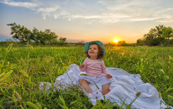 Beautiful baby sitting on blanket at sunset Stock Photography