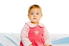 Beautiful baby sitting on a blue blanket. Studio Royalty Free Stock Images