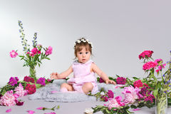 Beautiful baby sitting with a bouquet of flowers. Beautiful baby sitting with a bouquet of pink flowers Royalty Free Stock Photos