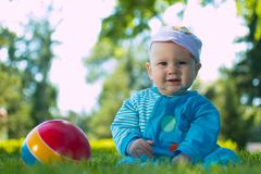 Baby sitting on the soft grass in the city Park with his colorful ball stock photo
