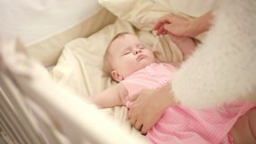 Beautiful baby sleeping in crib. Mother hands stroking sleeping kid stock footage