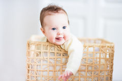 Beautiful baby smiling out of a wicker basket. Beautiful little baby smiling out of a wicker basket Stock Image