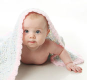 Beautiful baby under a blanket Stock Images