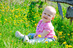 Beautiful baby in a village. Beautiful baby in a pink shirt and blue jeans sitting on the green grass in the countryside royalty free stock image