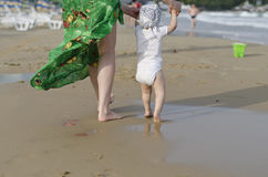 Beautiful baby walking on the sand Stock Images