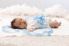 Beautiful baby in white bodysuit lying on back royalty free stock images