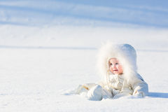 Beautiful baby in a white suit sitting in a snow field. On a very sunny winter day Stock Images