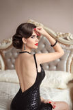 Beautiful back of elegant woman in black sexy dress posing on mo Royalty Free Stock Images