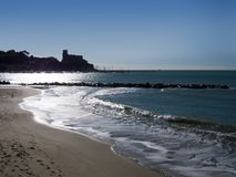 Silver sea at Lerici in Liguria, Italy. Popular tourist destinat. Beautiful back lit in winter showing shoreline, nobody Royalty Free Stock Photo