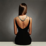 Beautiful Back Of Young Woman In A Black Dress. Luxury. Beauty Brunette Sitting Girl Girl With A Necklace On Her Back Stock Photo