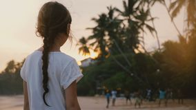 Beautiful back view shot of little 6-8 years old happy girl on tropical exotic sea beach watching sunset and people. Beautiful back view shot of little 6-8 stock video
