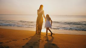 Beautiful back view shot of young happy mother and daughter walking to amazing sunset on golden sea beach together. stock video