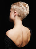 Beautiful back of young woman in a black sexy dress. Beauty blonde Girl with short haircut. fashion hairstyle Royalty Free Stock Images