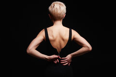 Beautiful back of young woman in a black sexy dress. Beauty blonde Girl with short haircut. fashion hairstyle Stock Photo