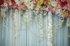Beautiful backdrop. colorful flowers arrangement over curtain. Beautiful flower wedding decoration, Colorful Flowers on curtain design for wedding background royalty free stock image