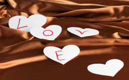 The beautiful backdrop of silk and paper heart. The beautiful backdrop of silk and five paper heart with the text Love. Holiday Cards Stock Images