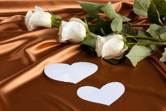 The beautiful backdrop of silk,  roses and heart. The beautiful backdrop of silk, white roses and two heart. Holiday Cards Stock Photography