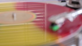 Beautiful background colorful vinyl record player rotates on the turntable. Reflection of a window with blinds on the surface of the vinyl stock video