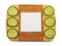 Beautiful background. Cucumber and notepad on wooden cutting board Royalty Free Stock Image