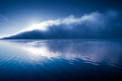 Beautiful background fog over river shiny wave. Glamorous background in shades of blue with big mist cloud with sun on river Stock Photos
