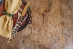 Beautiful background in hunting style: napkin, cutlery and pheasant feather on the rustic wooden background with copy space. Beautiful background in hunting royalty free stock photography