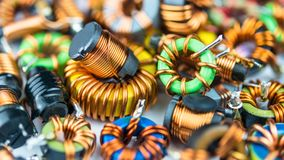 Colorful coils with magnetic core and copper winding. Beautiful background from inductors with small depth of sharpness. Concept for research, development Royalty Free Stock Images