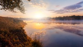 Beautiful background of nature. wonderful misty landscape. amazing foggy morning, colorful sky reflected in the water of tranquil. Lake. picturesque dramatic royalty free stock image