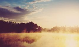 Beautiful background of nature. wonderful misty landscape. amazing foggy morning, colorful sky reflected in the water of tranquil royalty free stock photography