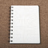 Beautiful background. Notebook on brown canvas background Stock Photos